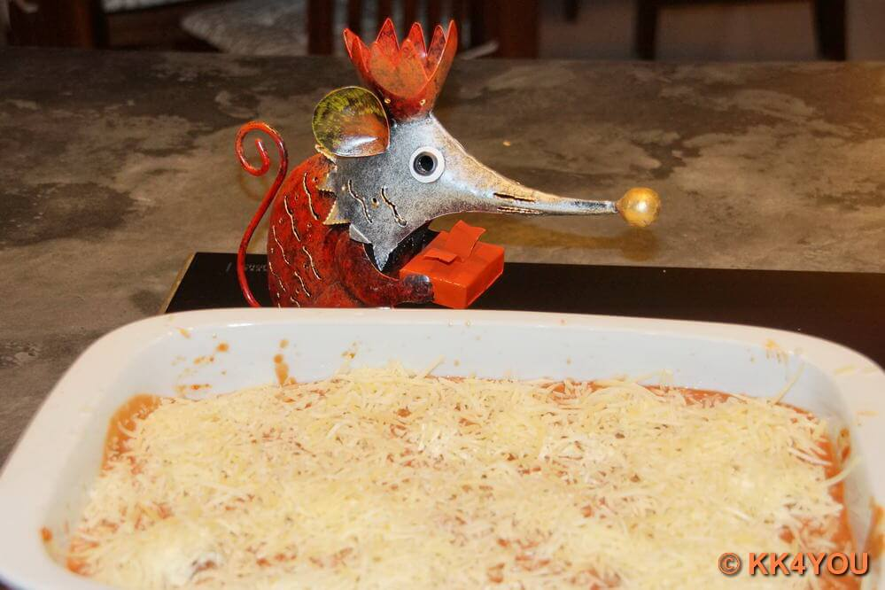 Tomatensauce und Käse über die Cannelloni geben