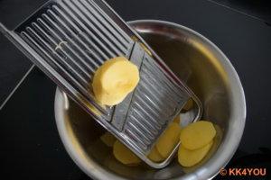 Kartoffeln schälen und in dünne Scheiben schneiden