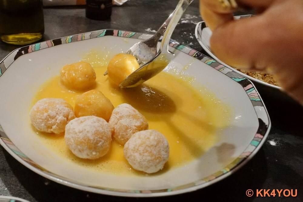 Käsebällchen im Mehl wenden, portionsweise durchs Ei ziehen