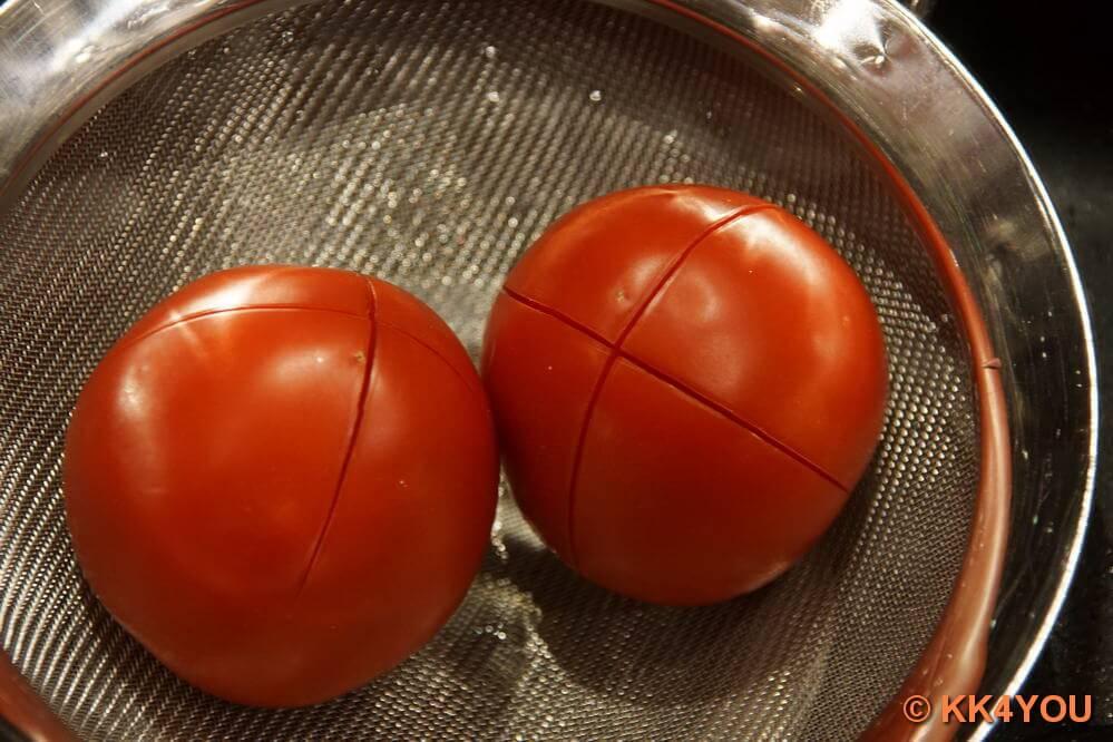 Tomaten über Kreuz einritzen, kurz überbrühen, kalt abschrecken und enthäuten.
