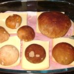 Steinpilzköpfe auf der Käse- Schinken- Kartoffellage