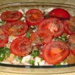 abgedeckt mit Tomatenscheiben und Gewürzen